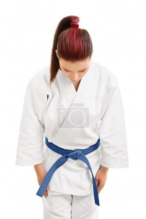 Photo for A portrait of a young girl in a white kimono with blue belt bowing, isolated on white background. - Royalty Free Image