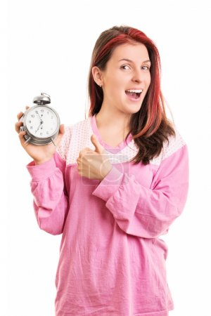 Young girl holding an alarm clock and thumbs up