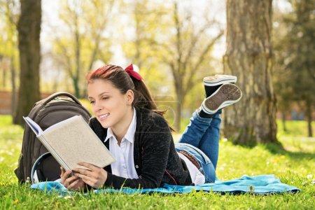 Photo pour Étudiant allongé sur une prairie lisant un livre. Fille lisant un livre dans le parc . - image libre de droit