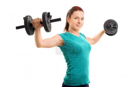 Photo for Hold them up! Young girl lifting dumbbells isolated on white background. - Royalty Free Image