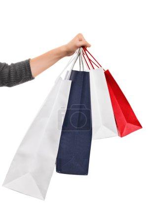Female hand holding shopping bags isolated on white background
