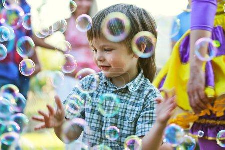 Boy among soap bubbles
