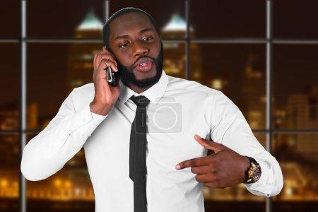 Photo pour Convaincre de parler au téléphone. Poste de nuit en centre d'appels. Homme noir ayant la conversation de l'entreprise. Siège de l'entreprise dans la nuit. - image libre de droit
