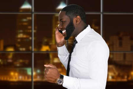 Happy businessman talks on the phone at night