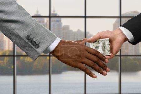 Manager handing money indoors.