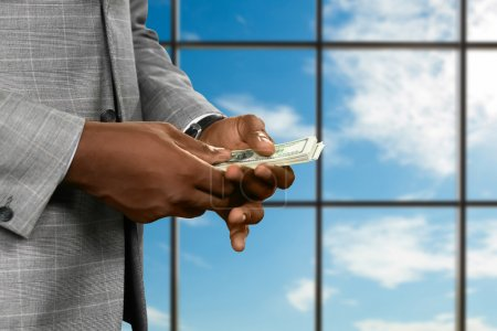 Businessman counts money near window.
