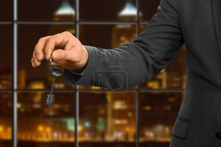 Night office worker holding key.