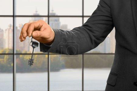 Businessman with key beside window.