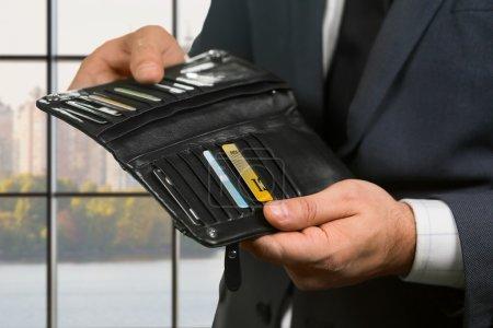 Photo pour Cartes en plastique à l'intérieur du portefeuille d'hommes d'affaires. Le gestionnaire vérifie à l'intérieur du portefeuille. Choisir quel endroit est moins cher. Petites décisions dans la grande ville. - image libre de droit