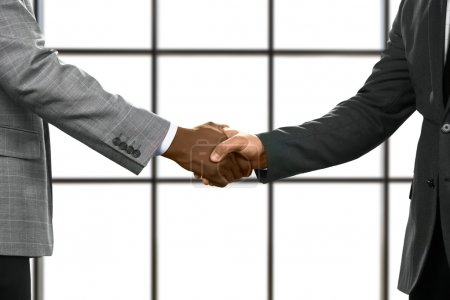 Businessmen shake hands in headquarters. Managers ...