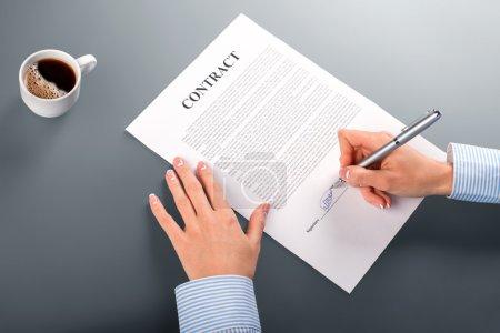Photo pour Femme gestionnaire signant le contrat. La femme met la signature sur le contrat. Matin à notre bureau. Im satisfait des conditions. - image libre de droit