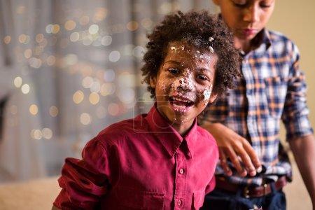 Photo pour Afro gamins visage enduit de gâteau. Un gamin noir enduit de gâteau. On s'amuse avec le dessert. Maman ne me croira pas. . - image libre de droit