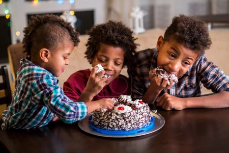 Three afro boys eating cake.