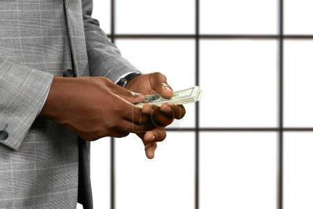 Black businessmans hands holding money.