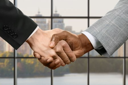 Businesspeople shake hands.