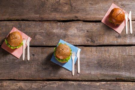 Photo pour Hamburgers sur des bâtons avec des couverts. Coutellerie avec hamburgers sur table. Nouvelle recette de hamburgers grillés. Nourriture populaire parmi les clients de café. - image libre de droit