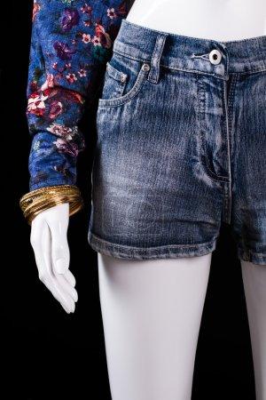 Denim shorts and gold bracelet.