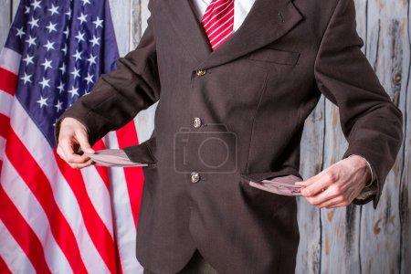 Businessman shows empty pockets.