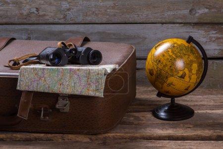 Photo pour Jumelles et carte sur valise. Globe à côté de la valise marron. Va où tu veux. La liberté est un trésor . - image libre de droit