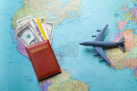 Photo pour Passeport et avion jouet. Carte avec passeport et argent. Choisissez la meilleure destination. Voler à travers l'océan . - image libre de droit