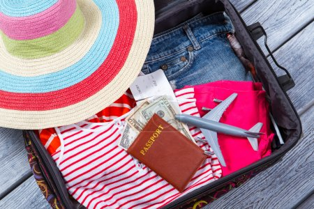 Photo for Suitcase with clothes and passport. Toy plane and beach hat. Luggage on wooden shelf. Airplane ticket for summer trip. - Royalty Free Image