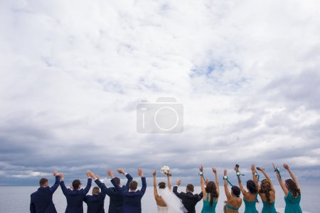 Guests on the wedding celebration are holding their hands up.
