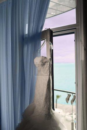 Photo pour La jolie robe de mariée est suspendue à la fenêtre de la chambre d'hôtel . - image libre de droit