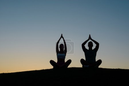 Photo pour Morning yoga on the nature. Silhouette figures of people at sunset. People relax. Rest at nature. Boy and girl meditating at sunset. - image libre de droit