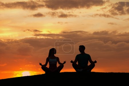 Man and  woman meditating in the mountains.