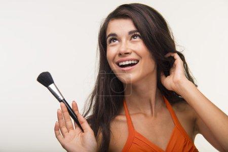 Photo pour La brune aux cheveux longs tient la brosse de maquillage. La belle fille dans la chemise orange sourit. - image libre de droit