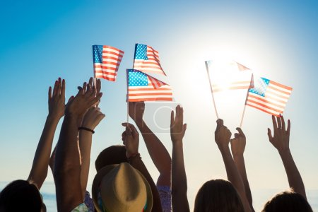 Young people waving American flags at sunset.