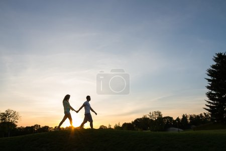 Lovers walk holding by hands.