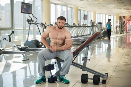 Photo for Strong man sitting on the bench in gym. Dumbbells on the floor. Girl on the background in gym. - Royalty Free Image