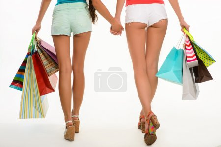 Buttocks of girls holding shopping bags.