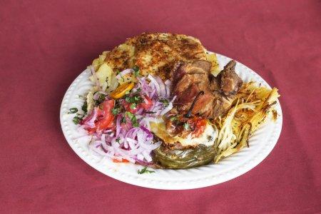 """Foto de Plato peruano: """"Doble"""" de Arequipa. Frito cerdo (chicharrón), rompieron patatas (pastel de papa), cebolla, tomate, espaguetis con queso (tallarin de queso) y pimienta caliente rellena con carne (rocoto relleno). - Imagen libre de derechos"""