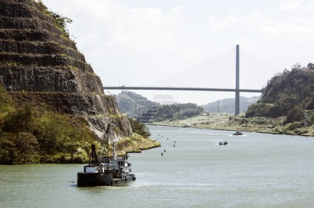 Passing Panama Canal near the bridge with small tug.