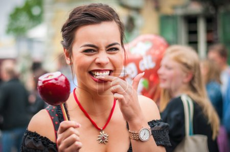 Attractive woman holding a red caramelized apple at the Oktoberfest