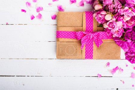 Photo pour Fond vintage avec un cadeau et des fleurs sur une surface en bois - image libre de droit