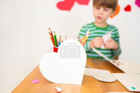 Photo for Kids, children, doing Valentine's day arts and crafts with hearts, pencils, paper - Royalty Free Image