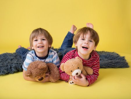 Photo for Two happy kids, brothers or friends, having fun, playing games, and hugging their stuffed toys - Royalty Free Image