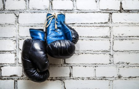Photo for Pair of old blue boxing gloves hanging on white brick wall background. - Royalty Free Image