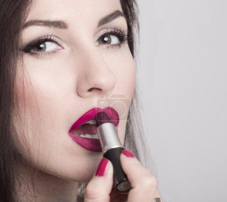 Close-up of woman applying lipstick. Model looks like Monica Bellucci.
