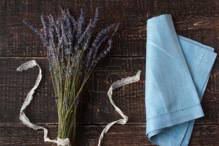 Foto de Lavender bouquet with a white stripe and a blue napkin on the dark wooden table horizontal - Imagen libre de derechos