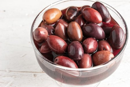 Kalamata olives on the glass bowl on the old wooden table
