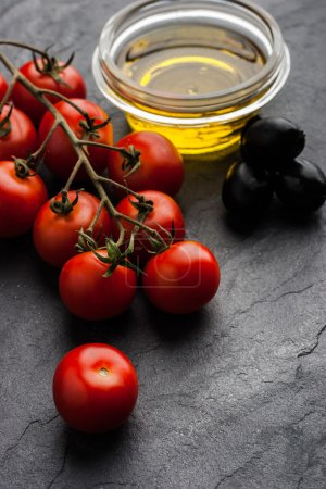 Photo for Twig of red tomatoes with black olives ; and olive oil on the black stone table - Royalty Free Image