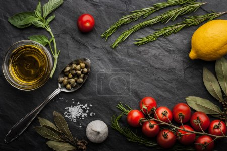 Foto de Green basil ,rosemary and bay leaf with salt , tomatoes , lemon ,capers, garlic and olive oil on the black stone  table - Imagen libre de derechos