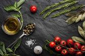 """Постер, картина, фотообои """"Травы смешать с помидорами и оливковым маслом на черном каменном столе"""""""