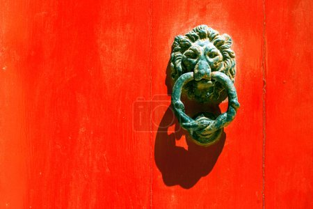 Old forged maltese handle on the red door