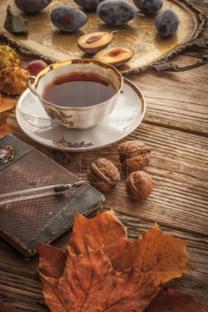 Photo for Cup of tea with plums , chestnuts , maple leaves, nuts , brass tray  and vintage notebook on the wooden table   with film filter effect  vertical - Royalty Free Image