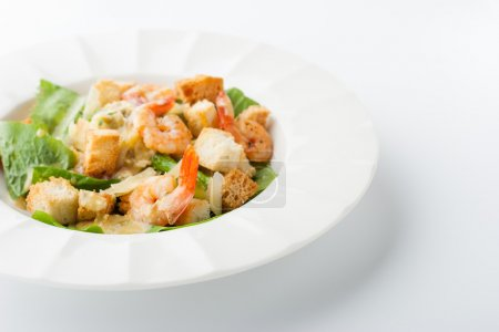 Caesar salad with shrimps on the white background horizontal